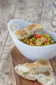 picture of curry chicken  - Bowl with curry flavored rice chicken and vegetables on rustic wooden table