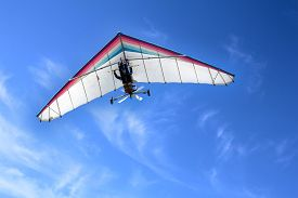 picture of glider  - The motorized hang glider in the blue sky - JPG