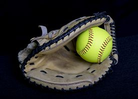 stock photo of softball  - A fastpitch softball catchers mitt with a yellow fastpitch softball in the webbing - JPG