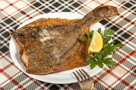 image of flounder  - Fried flounder on a plate decorated with parsley and lemon - JPG