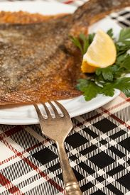 stock photo of flounder  - Fried flounder on a plate decorated with parsley and lemon - JPG