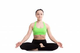 stock photo of pranayama  - Serene fitness girl does yoga training sitting in Ardha Padmasana half lotus posture Siddhasana Accomplished Pose asana for meditation breathing exercises - JPG