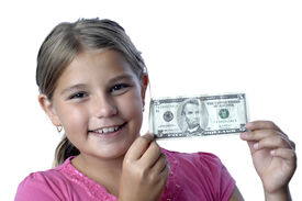 picture of little school girl  - School girl is playing with a paper bills before putting them into the piggy bank - JPG
