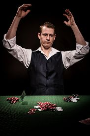 stock photo of gambler  - A male gambler is upset after losing and throw the cards away - JPG