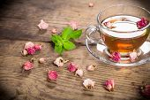 stock photo of rose bud  - Cup of green tea with mint and dried rose buds on old wooden desk - JPG
