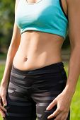 foto of abdominal muscle  - Fit woman showing her abdominal muscles outdoors - JPG