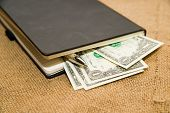 stock photo of memento  - notebook with a blank sheet pen and money on the old tissue - JPG