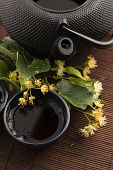 stock photo of teapot  - teapot and cup with linden tea and flowers - JPG