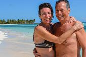 foto of crystal clear  - Happy couple on a beautiful deserted beach with turquoise and crystal clear waters of the Caribbean sea in the Dominican Republic on the island of Saonna - JPG