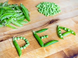 stock photo of pea  - Word PEA created with peas on a wooden board with peas and pods in the background - JPG