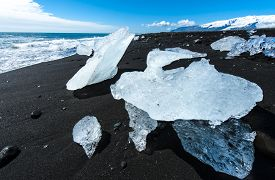 image of iceberg  - Beautiful beach in the South of Iceland with a black lava sand is full of icebergs from glaciers not far away - JPG