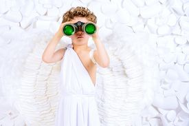 picture of cupid  - Cute little boy in a costume of angel looking through the binoculars - JPG
