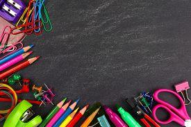 stock photo of chalkboard  - School supplies bottom corner border on a chalkboard background - JPG