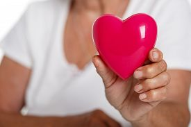 stock photo of resuscitation  - Elder woman holding red toy heart in front of her chest - JPG