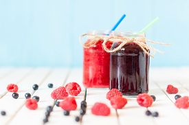 image of jar jelly  - Rustic Mason Jars with raspberry jam and bog bilberry marmalade with fresh berries on white wooden background - JPG