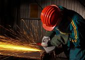 stock photo of industrial safety  - heavy industry manual worker with grinder - JPG