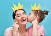 Funny family on a background of bright blue wall. Mother and her daughter girl with a paper accessor poster