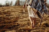 Woman Legs In Native Indian American Boho Dress Walking In Windy Sunny Evening Mountains, Holding Fe poster