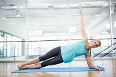Fit blonde doing exercise on mat in fitness studio poster