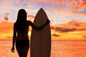 Beach sunset sexy surfer woman surfing lifestyle relaxing holding surfboard looking at ocean waves f poster