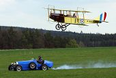 Race between Bugatti car a by historic plane Curtiss Jenny in airport Plasy - Czech Republic Europe
