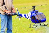 Piloting Radio controlled helicopter (scale-model 1:24 scale) with remote control. Teleobjective sho