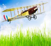 Flying biplane (homemade radio controlled scale-model 1:24 scale) over fresh spring grass on a airfi