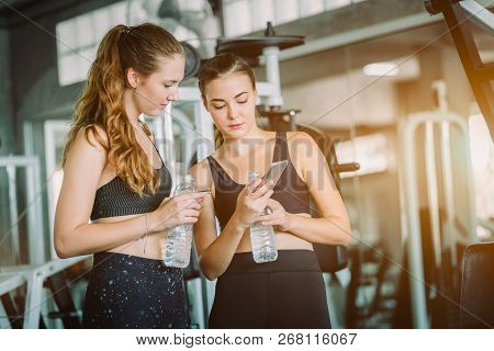 poster of Fit Beautiful Young Woman Athletes In Fitness Clothes Relaxing After Workout In Gym. Couple Women St
