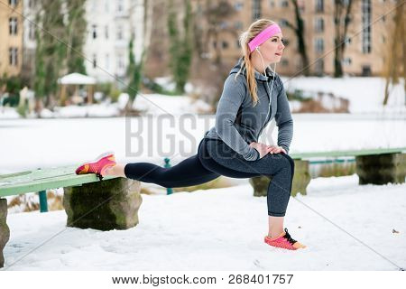 poster of Fit woman stretching her limbs for sports exercise in winter