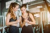 Fit Beautiful Young Woman Athletes In Fitness Clothes Relaxing After Workout In Gym. Couple Women St poster