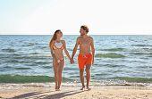 Happy Young Couple In Beachwear Posing On Seashore poster