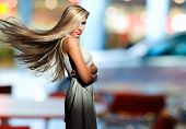 stock photo of flutter  - Portrait of the blonde with  flyaway hair in the background of city - JPG