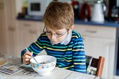 Adorable Happy Little Blond Kid Boy With Glasses Eating Homemade Cereals For Breakfast Or Lunch. Hea poster