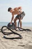 Young Handsome Attractive Man Doing Fitness Workout At A Beach On A Sunny Day. Bare Chested Man Doin poster