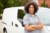 Young black female tradesperson standing next to her white van with arms crossed, close up poster