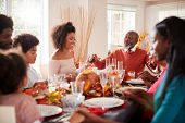 Multi generation mixed race family holding hands and saying grace before eating at their Thanksgivin poster