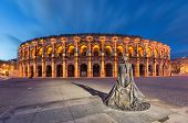 Nimes, France. Roman Amphitheater (arena Of Nimes) At Dusk And Monument To Bullfighter poster