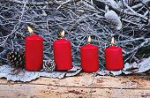 Four Red Burning Advent Candles As Catholic Symbol Of Christmas. Christmas Decoration With Burning C poster