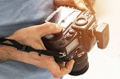 Digital Single Lens Reflex Camera In Male Hands. Photographer Shooting Hands Close Up. Man Photograp poster