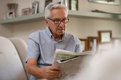 Portrait of elderly man reading newspaper while sitting on couch. Retired man wearing spectacles whi poster