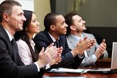 stock photo of applause  - Multi ethnic business group greets somebody with clapping and smiling - JPG