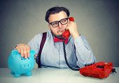 Chubby Business Man Sitting With Piggybank At Table And Having Dull Phone Conversation Looking Annoy poster