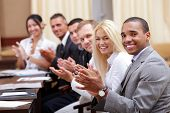 stock photo of applause  - Multi ethnic business group greets you with clapping and smiling - JPG