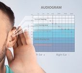 Young Man With Symptom Of Hearing Loss And Audiogram On Color Background. Medical Test poster