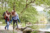Four adult friends during a hike, men piggybacking their girlfriends poster
