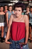 foto of cynicism  - Lonely girl with hunched shoulders near group of people - JPG