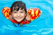 pic of cortez  - a cute little girl with hazel eyes wearing an inflatable life vest having fun in swimming pool - JPG