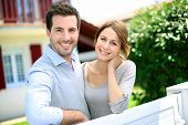 stock photo of in front  - Cheerful couple standing in front of new house - JPG