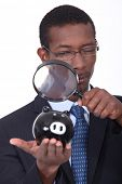black well dressed man watching a piggy bank with a magnifying glass