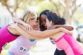 foto of pep talk  - Female Runners Congratulating One Another After Race - JPG